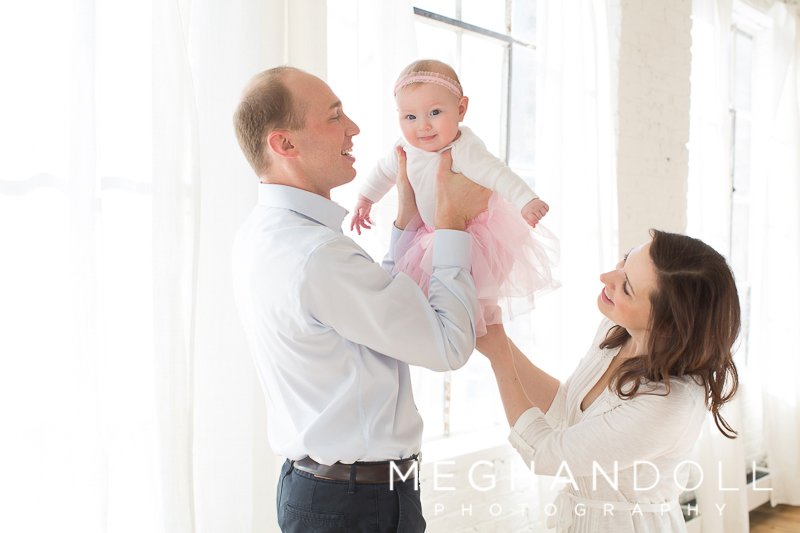 mom-and-dad-play-with-baby-girl-in-pink-tutu