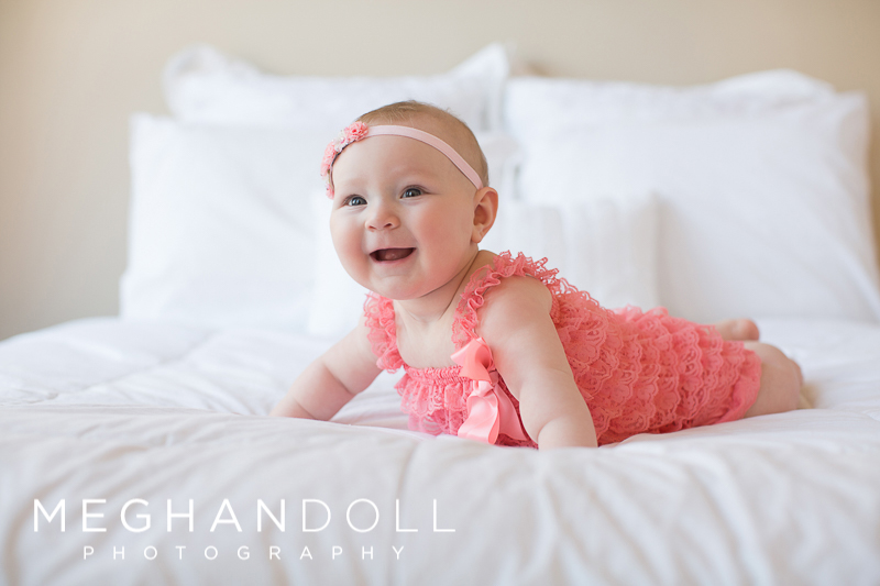 six-month-baby-girl-rolls-onto-her-tummy-in-coral-romper