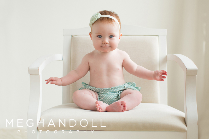 six-month-old-red-headed-baby-girl-sits-up-in-big-white-chair