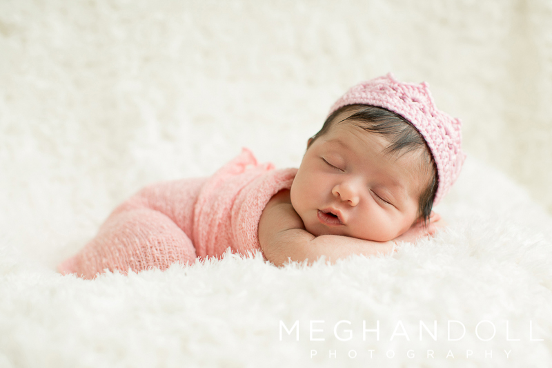 little-princess-baby-in-crown-sleeps-on-white-blanket
