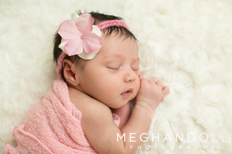 snuggly-newborn-baby-girl-in-pink-on-fluffy-white-blanket