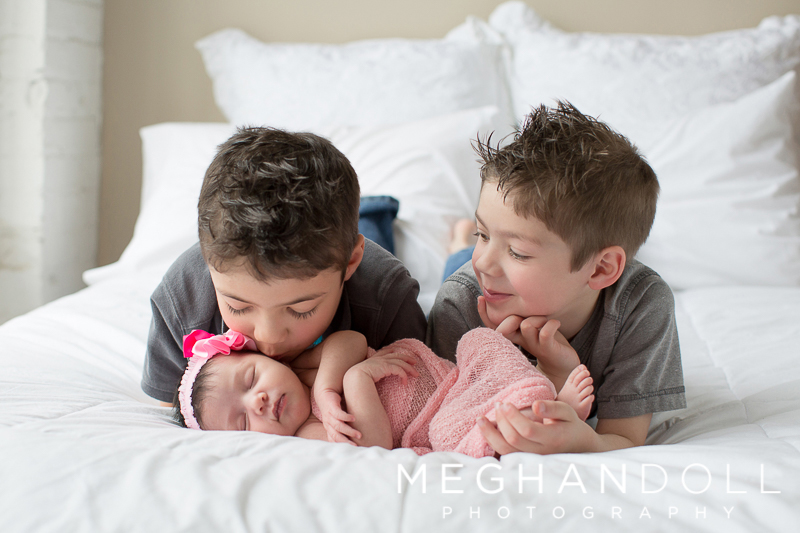 sweet-biggest-brother-gives-new-sister-a-kiss-while-other-brother-looks-on