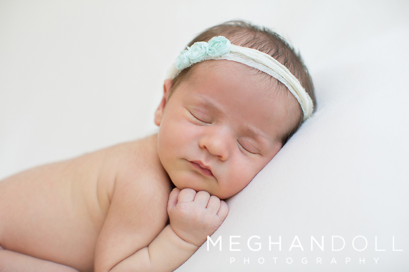 sweet-newborn-girl-sleeps-with-a-blue-headband-on-milky-white-blanket