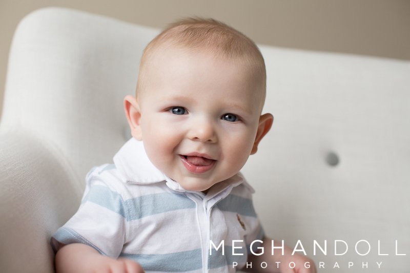 six-month-old-baby-boy-sits-on-button-couch-with-big-smile