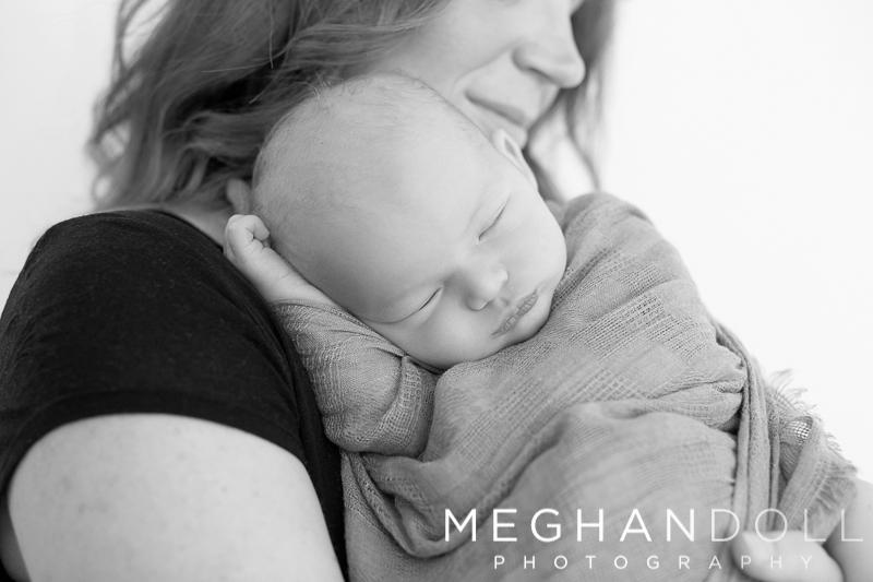 little-newborn-boy-snuggles-on-mom's-shoulder