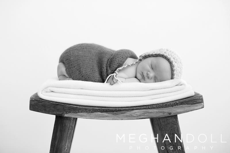 tiny-little-newborn-boy-sleeps-atop-a-wooden-bench