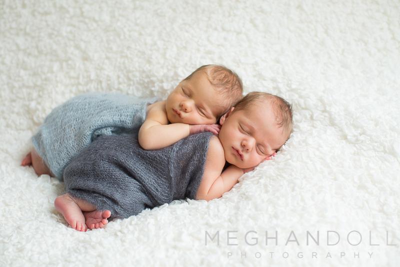 newborn-twin-boys-snuggle-in-gray-wraps-on-big-white-blanket