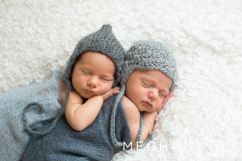 twin-newborn-brothers-in-knit-hats-sleep-sweetly-on-big-white-blanket