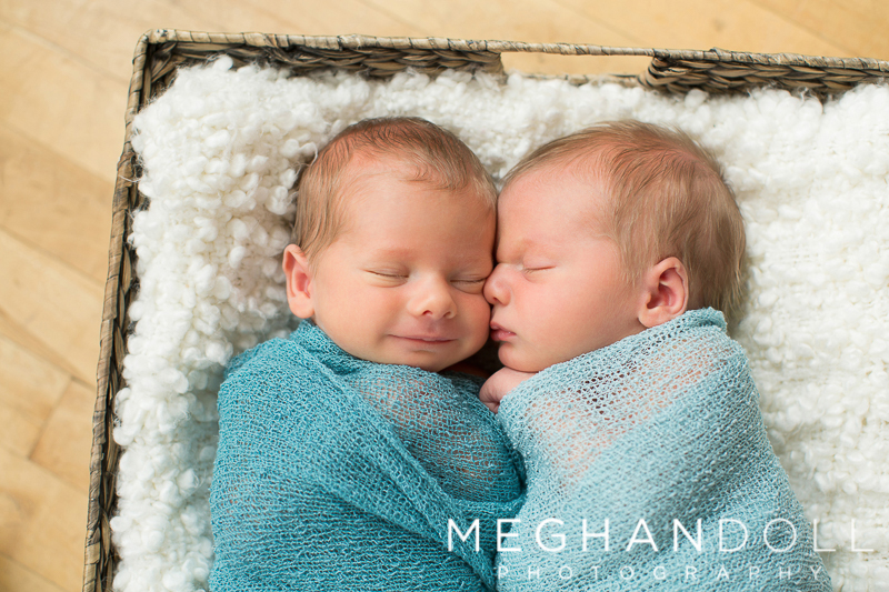 twin-newborn-brothers-snuggle-together-in-big-square-basket