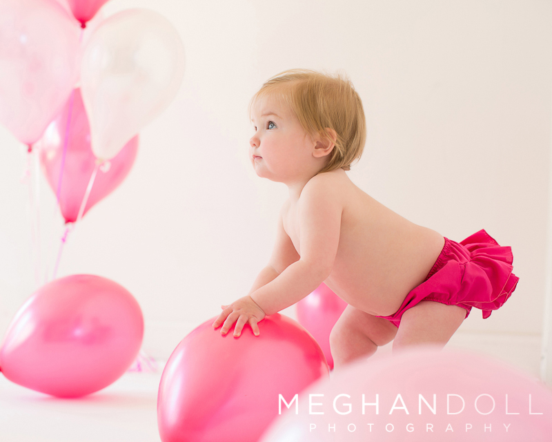 one-year-old-girl-plays-with-her-birthday-balloons