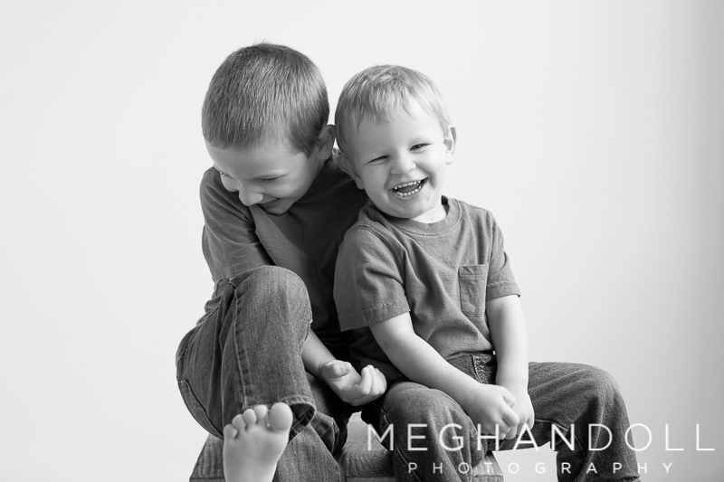 brothers-sit-and-laugh-together-on-big-gray-block
