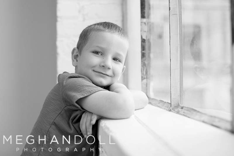 five-year-old-boy-smiles-sweetly-at-window