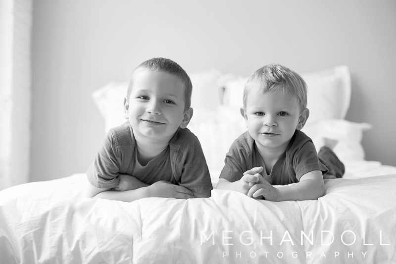 two-boys-pause-from-laughing-on-the-big-white-bed