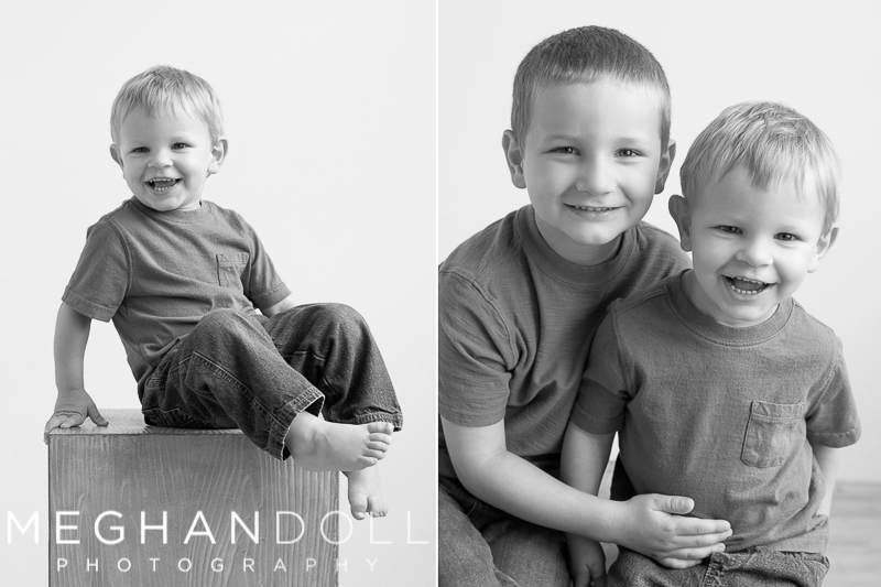 two-sweet-brothers-smile-together-and-two-year-old-sits-by-himself-on-big-block