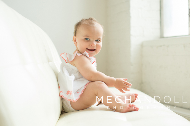 big-one-year-old-girl-sits-on-big-white-couch