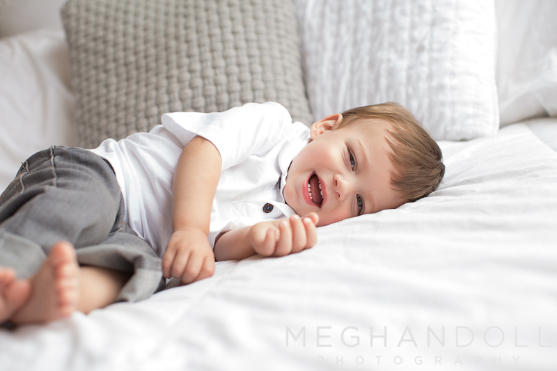 little-twin-one-year-old-boy-rolls-around-on-big-white-bed