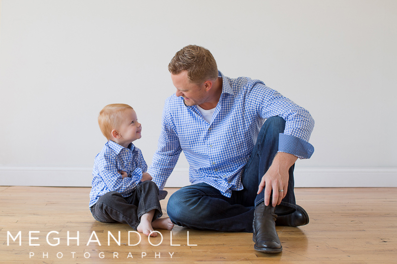 dad-and-two-year-old-son-sit-on-the-floor-and-look-at-each-other