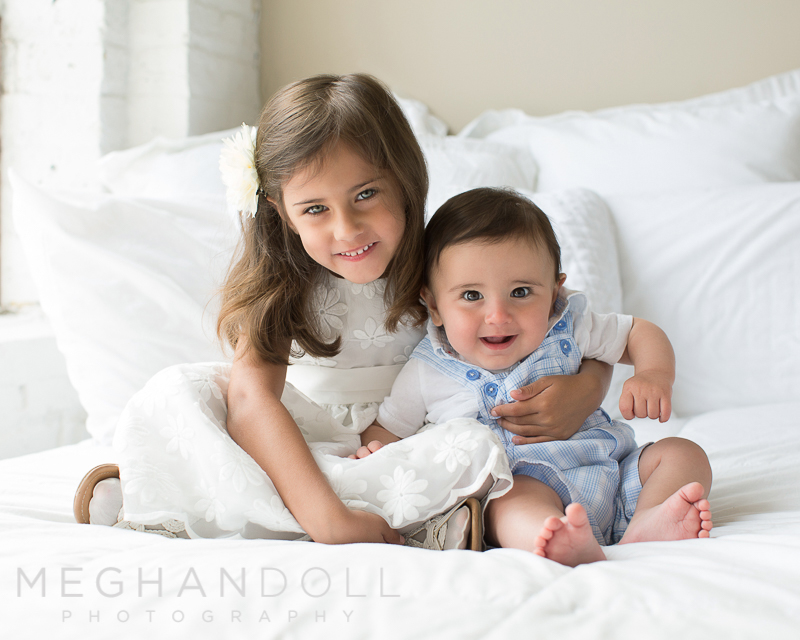 big-sister-holds-baby-brother-on-big-white-bed