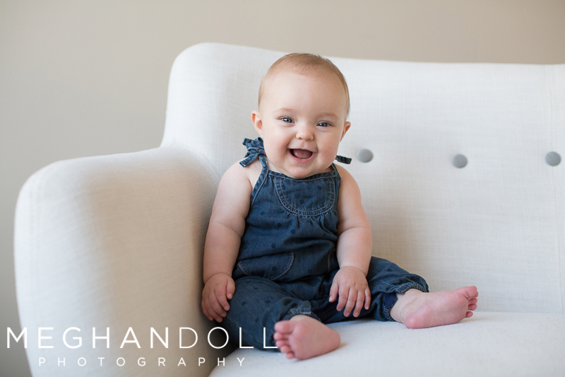 six-month-baby-girl-laughs-on-couch