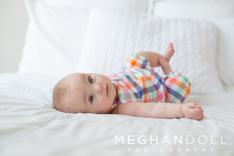 six-month-old-baby-girl-in-plaid-rolls-around-on-big-white-bed
