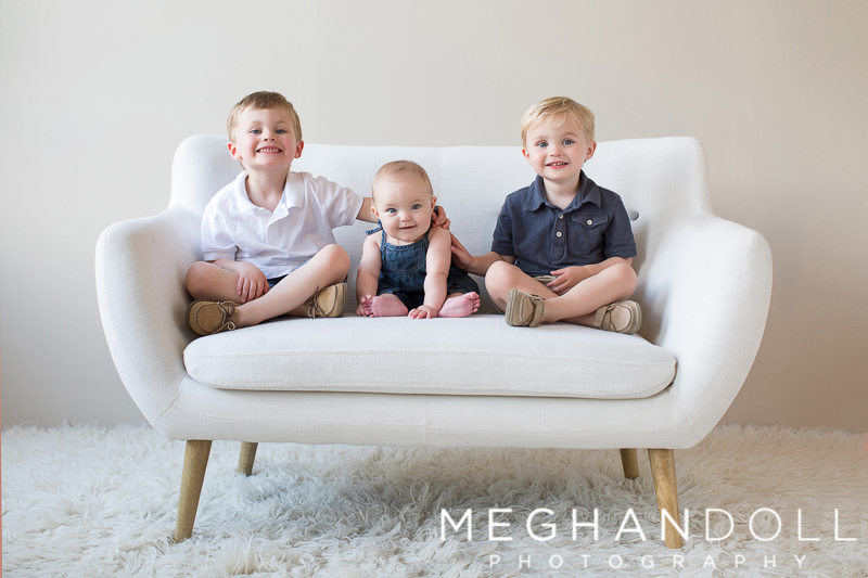 three-little-siblings-smile-on-a-small-couch