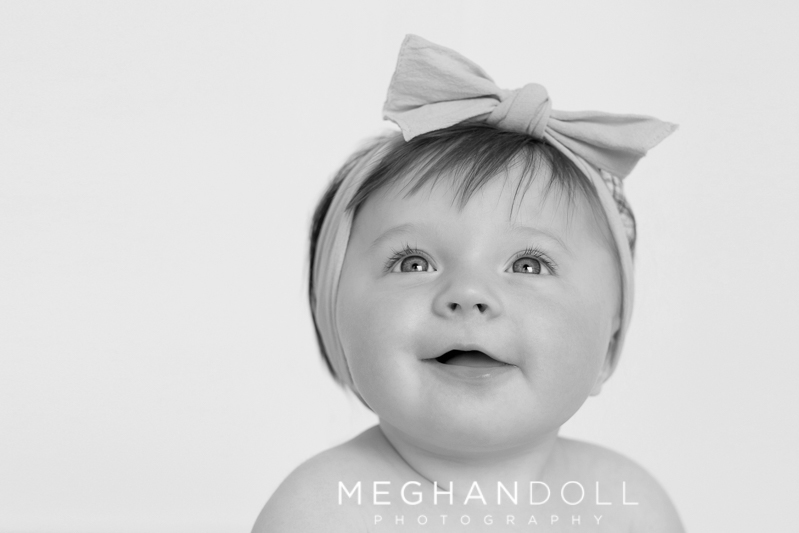 sweet-six-month-old-baby-girl-smiles-with-bow-headband