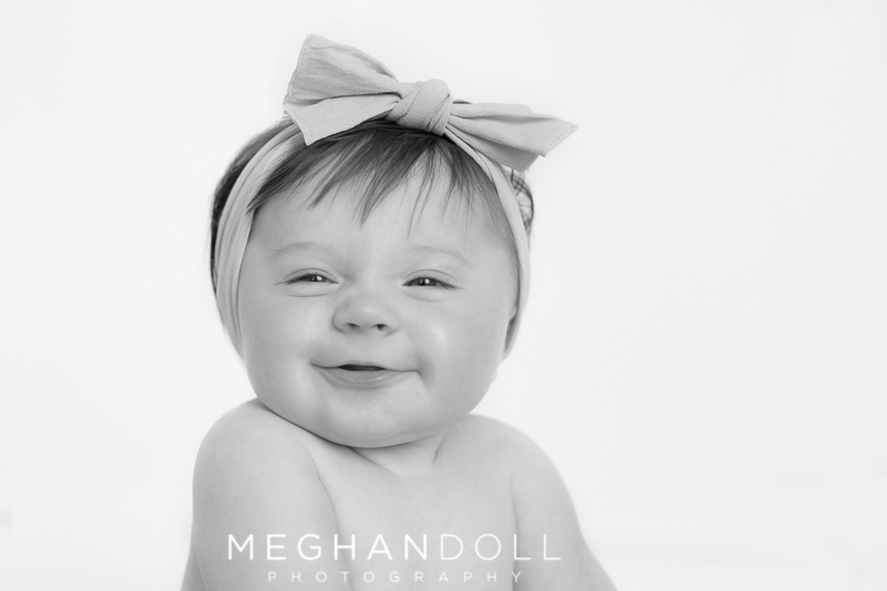 sweet-six-month-old-baby-girl-makes-silly-face-with-big-headband