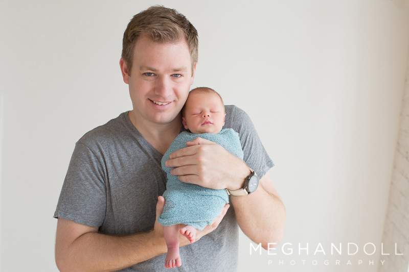 dad-smiles-and-shows-off-his-newborn-son