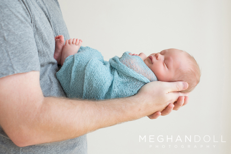 little-newborn-boy-in-teal-sleeps-in-dads-arms