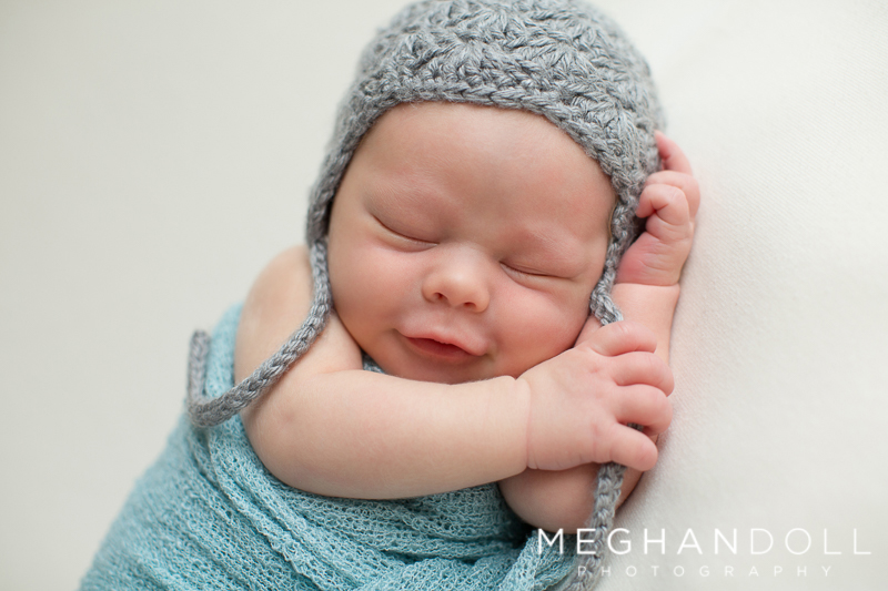 newborn-baby-boy-in-teal-smiles-with-little-gray-hat