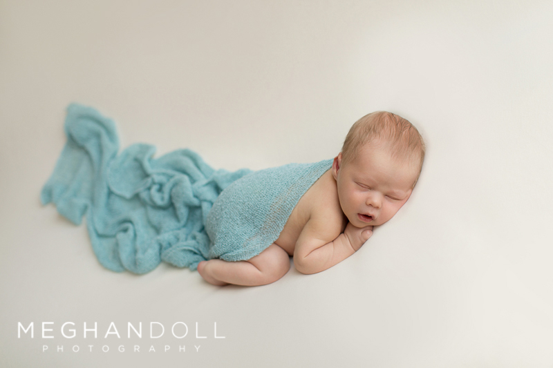 sweet-sleepy-newborn-in-teal-sleeps-on-big-white-blanket