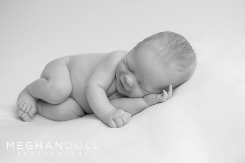 smiley-round-little-newborn-boy-on-solid-white-blanket