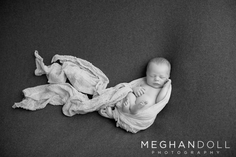sweet-newborn-boy-sleeps-on-big-gray-blanket-wrapped-in-light-cloth