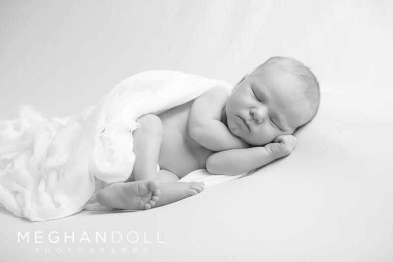 little-sleeping-newborn-boy-on-big-white-blanket