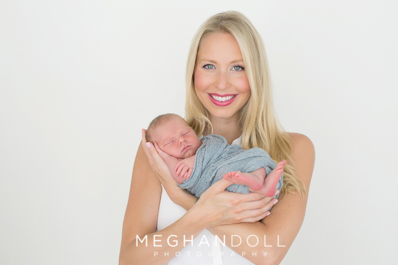 mom-smiles-proudly-while-holding-her-new-baby-boy