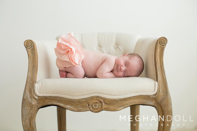 sweet-newborn-girl-in-ruffle-bloomers-sleeps-on-chair