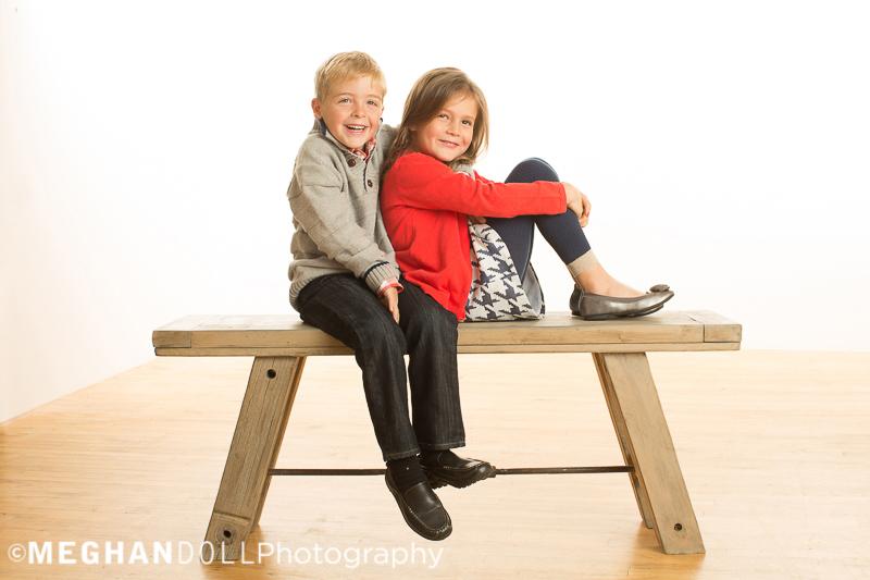 twin-siblings-snuggle-on-big-bench
