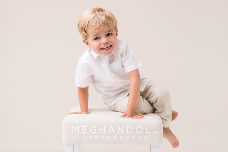 adorable-three-year-old-boy-in-white-laughs-on-stool