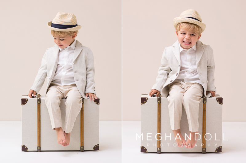 sweet-little-three-year-old-boy-in-fedora-hat-laughs-on-a-suitcase