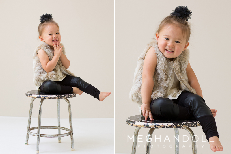 fashionable-two-year-old-girl-smiles-on-little-stool
