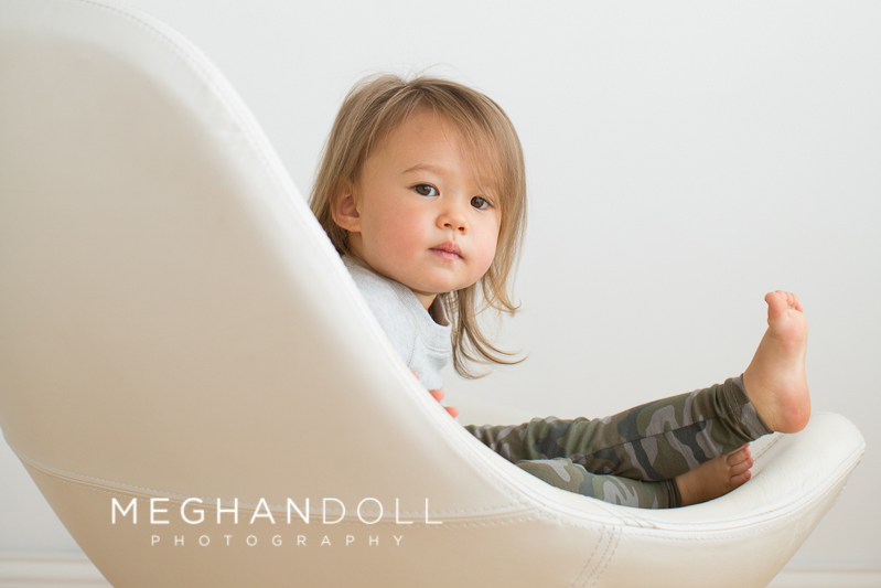 serious-two-year-old-girl-relaxes-in-big-chair