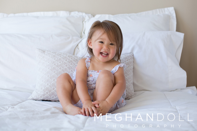 sweet-little-two-year-old-girl-sits-and-giggles-on-big-bed