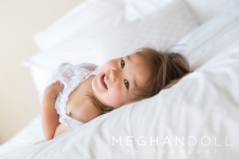 sweet-two-year-old-rolls-on-big-white-bed