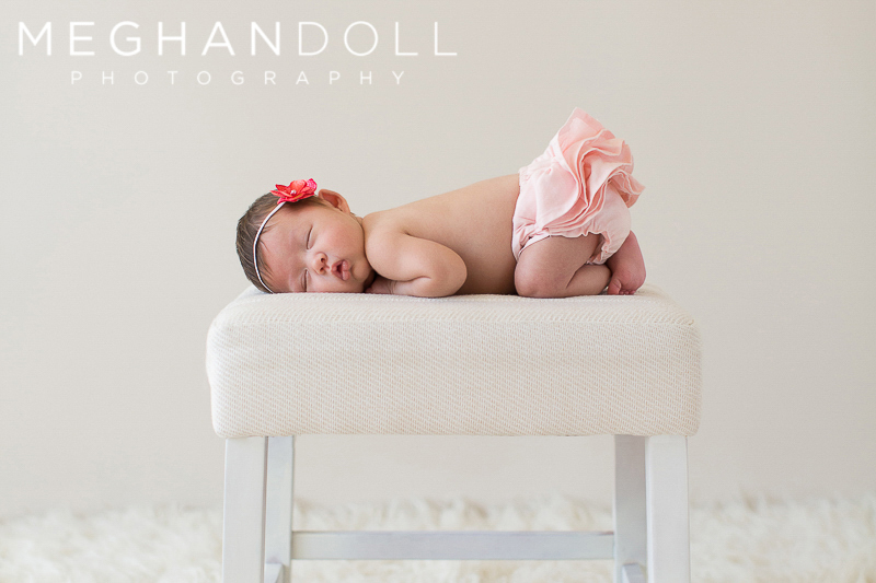 little-newborn-baby-girl-in-pink-ruffles-sleeps-on-stool