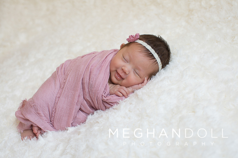 little-newborn-girl-smiles-in-pink-wrap