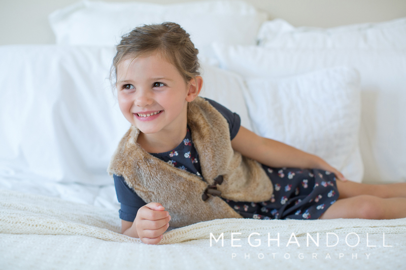 little-three-year-old-girl-in-furry-vest-lounges-on-big-white-bed