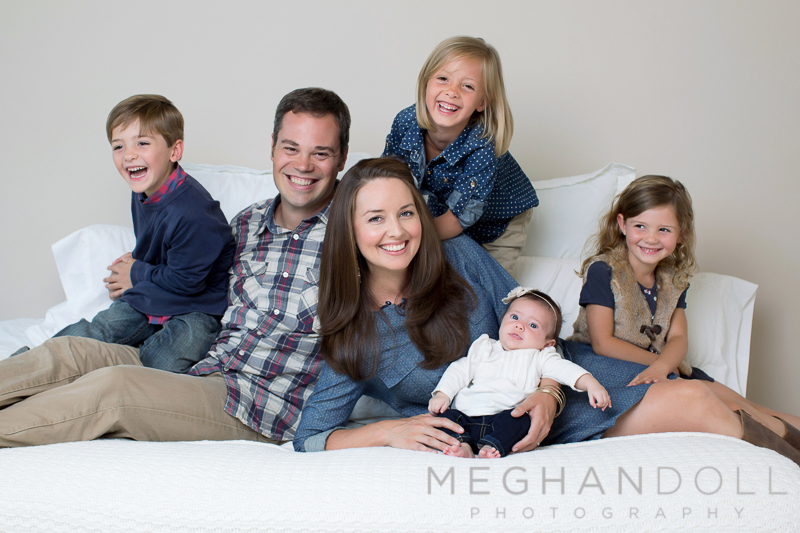silly-family-of-six-giggles-on-big-white-bed