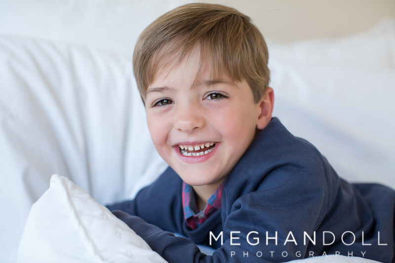 silly-five-year-old-twin-boy-laughs-on-big-white-bed