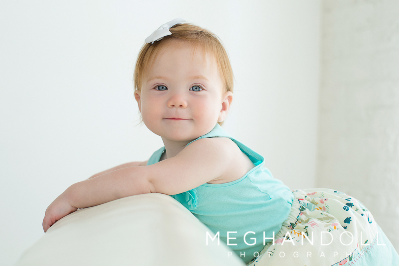 little-one-year-old-red-headed-baby-girl-leans-on-big-white-couch