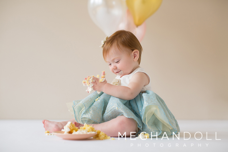silly-little-one-year-old-baby-girl-in-her-blue-tutu-plays-with-her-cupcake